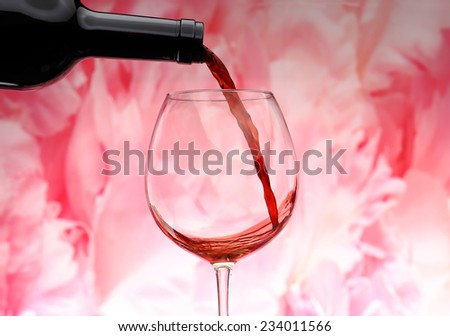Pouring red wine into glass and rose background