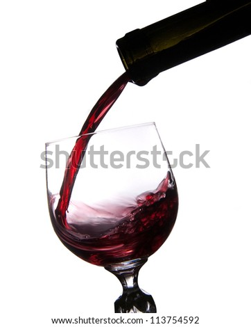 Pouring red wine into glass isolated