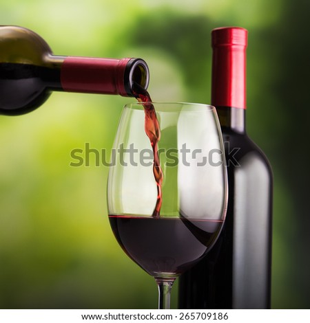 Pouring red wine into green natural background - stock photo