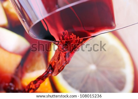 Pouring red wine into juice fruits - stock photo