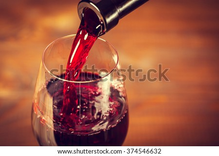 Pouring red wine into the glass against wooden background - stock photo