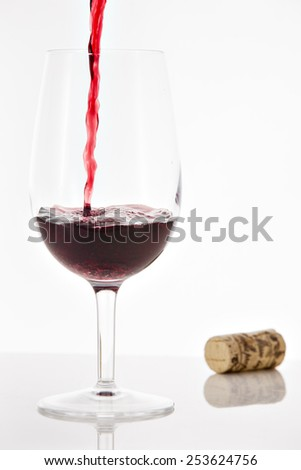 Pouring red wine into wineglass with splash on white background - stock photo