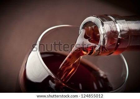 pouring red wine on background - stock photo