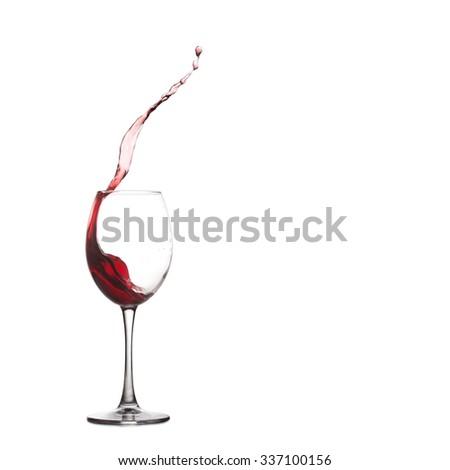 Pouring, red wine splash into glass,  wine glass splashing, close-up, white background. copy space - stock photo