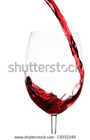 Pouring red wine splashes into a crystal wine glass - stock photo