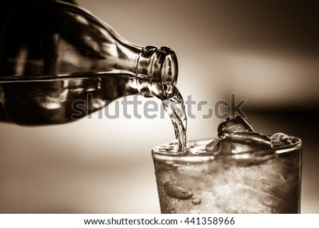 Pouring soda water from bottle into glass in sepia tone.Toned image,soft focus,film noir style. - stock photo