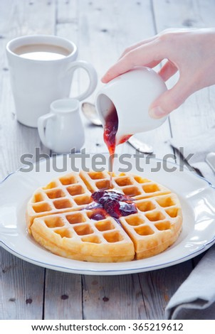 Pouring Strawberry Jam to waffles for breakfast - stock photo