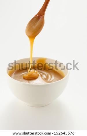 Pouring sweet caramel sauce - stock photo