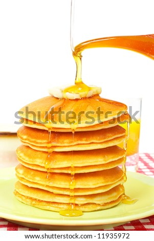 Pouring syrup on the big stack of pancakes with butter. Shallow depth of field - stock photo