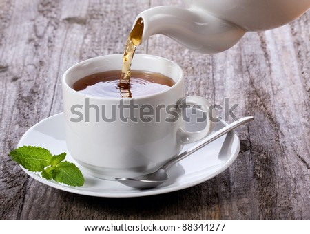 Pouring tea into cup of tea - stock photo