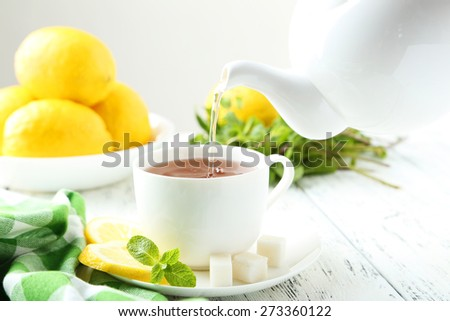 Pouring tea into cup of tea on white wooden background - stock photo