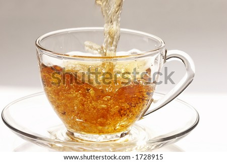 Pouring tea into glassy tea cup - stock photo