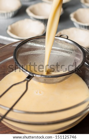 Pouring the mixture through a sieve into a glass bowl for smooth mixture egg custard cream. - stock photo