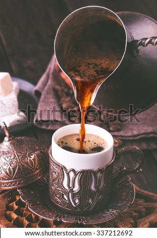 Pouring turkish coffee into traditional embossed metal cup.Toned - stock photo