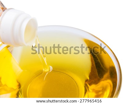 Pouring vegetable cooking oil into a clear glass bowl  - stock photo