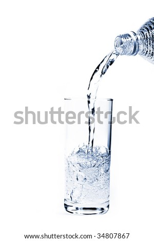 Pouring water from a bottle into a glass against a white background - stock photo