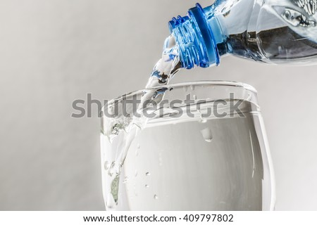 Pouring water from bottle into glass c - stock photo