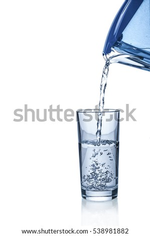 Pouring water from filter pitcher in glass on white background