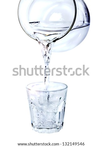 Pouring water from glass pitcher on white background - stock photo