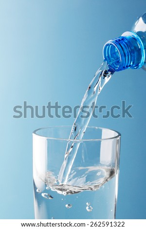 Pouring water from plastic bottle into glass on blue background - stock photo