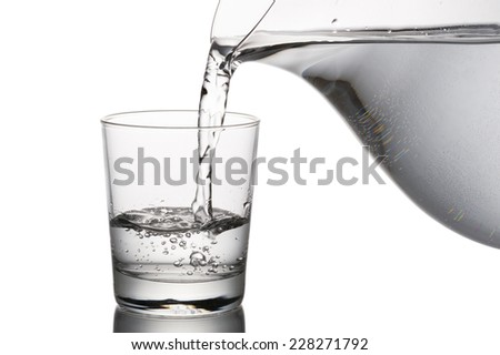 pouring water into glass from a carafe, on white background - stock photo