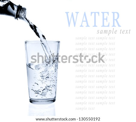 Pouring water into glass isolated on white background