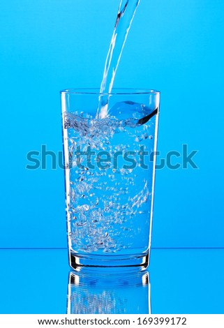 Pouring water into glass on blue background - stock photo