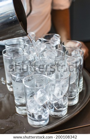 pouring water into the glasses with ice from a stainless steel pitcher - stock photo