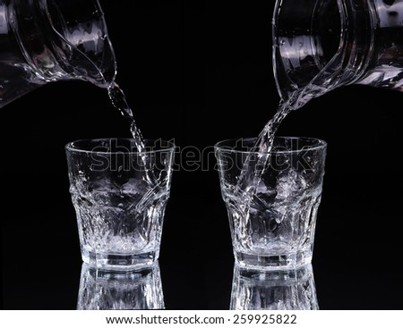 pouring water on a glass on black background