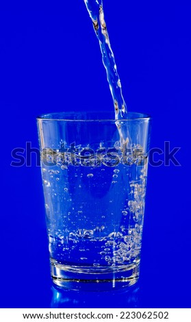 pouring water on a glass on blue background - stock photo
