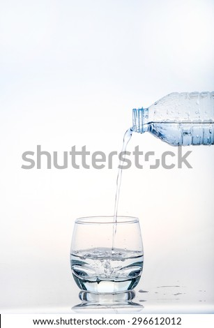 pouring water on a glass on white background,Glass of water, Glass of water isolated on white background,Water pouring from bottle into the glass, isolated on white