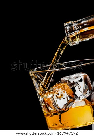 Pouring whiskey drink into glass - stock photo