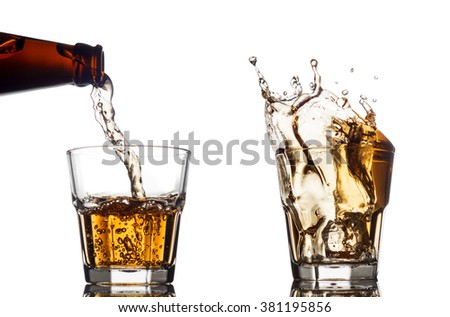 Pouring whiskey in a clear glass, on white background - stock photo