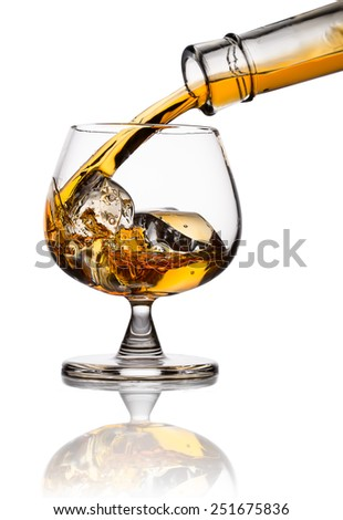 Pouring whiskey in glass with ice isolated on white - stock photo