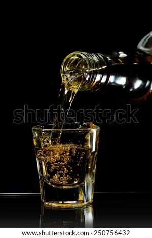 pouring whiskey into a shot glass against black - stock photo