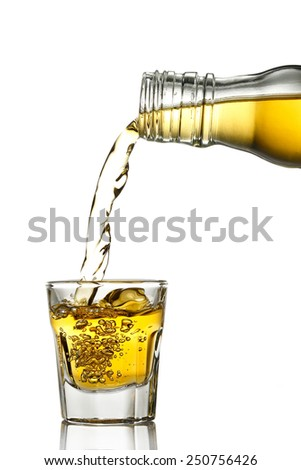 pouring whiskey into a shot glass isolated on white - stock photo