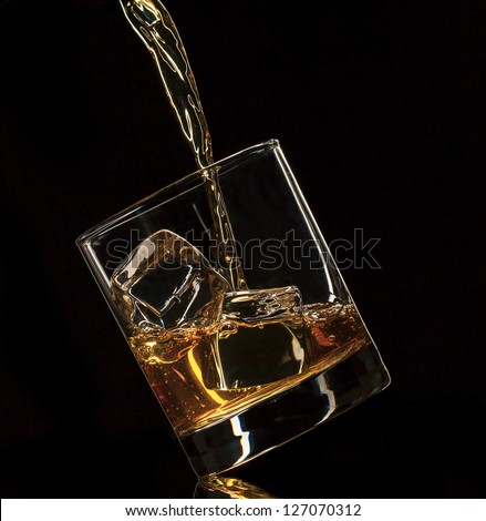 Pouring whiskey into glass, isolated on black background - stock photo