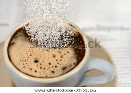Pouring white sugar into coffee cup