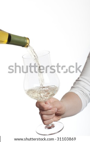 Pouring white wine into glass holding in hand on white background - stock photo