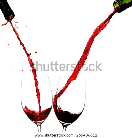 Pouring wine into two glasses isolated on white background - stock photo