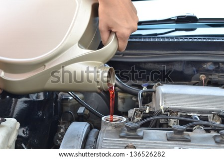 pours fresh oil into a car engine as part of its - stock photo