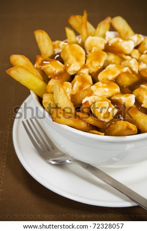 Poutine meal made with french fries, cheese curds and gravy. Very Shallow depth of field. - stock photo