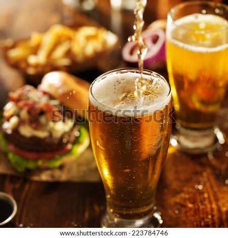 pouting beer into glass with burgers on wooden table top - stock photo