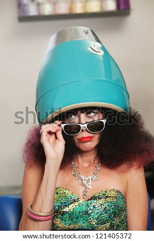 Pouting lady with frizzy hair sitting under hair dryer