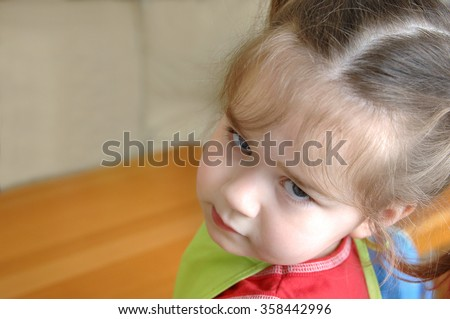 Pouting little girl, looks over her shoulder and stares at camera.  She is inside her home. - stock photo