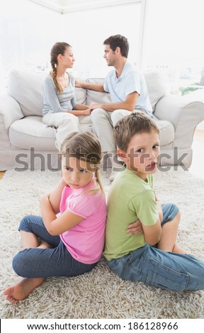 Pouting siblings sitting back to back while parents are arguing at home in the living room - stock photo