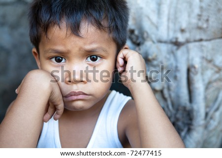 Poverty - portrait of a cute young Asian boy, Filipino male against wall with copyspace. - stock photo