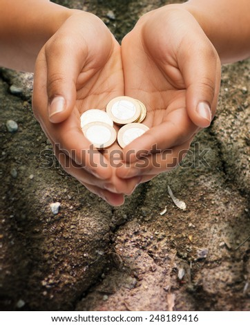 poverty, starvation, ecology and charity concept - closeup of female hands holding euro coins over ground background