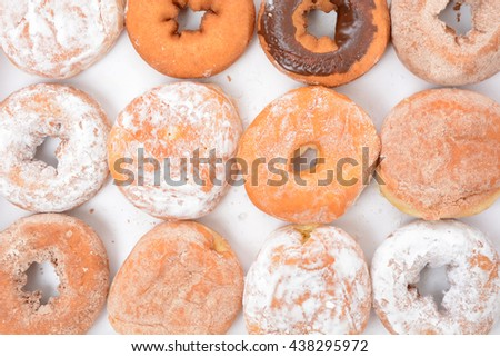 powder and chocolate donuts in a row