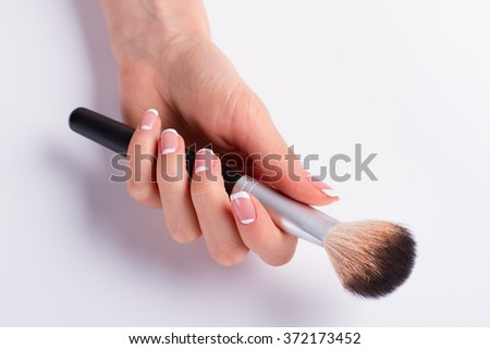 Powder brush in a female hand. Beautiful french manicure.